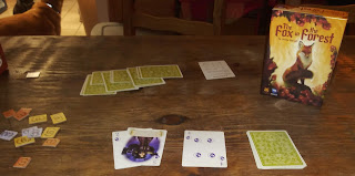 A game of The Fox in the Forest in progress. The box, with cover art depicting a fox sitting proudly atop a stone surrounded by flowering plants, stands near the draw pile, discard pile, and currently played cards. An array of cards, which are tricks taken by one of the players, sits nearby, along with a scoring summary and a pile of victory point tiles in 1, 3, and 6 point denominations.