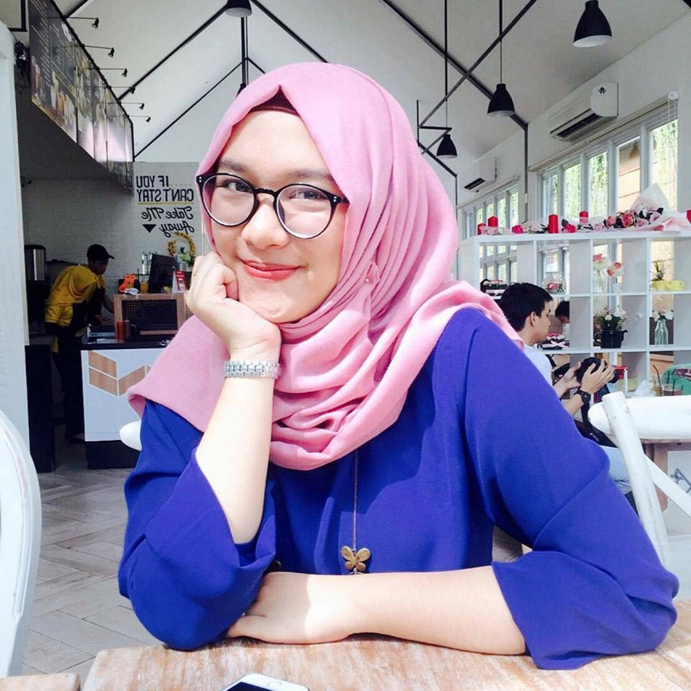 Cewek Berjilbab pink manis pakai Kacamata selfie di Cafe