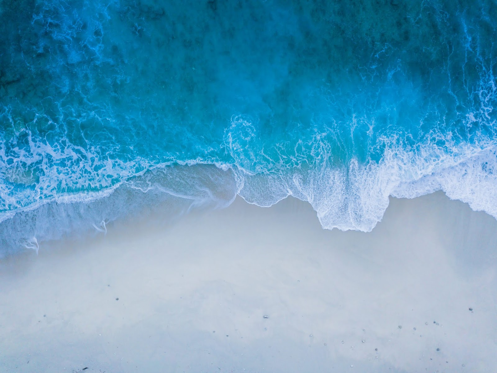 A photo taken from above of a beach as a wave crashes onto the sand. The Sea is at the top of the photo, the sand is at the bottom.