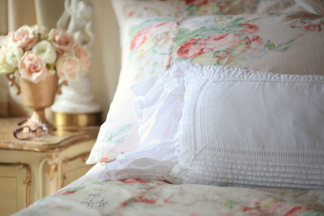 Floral bedding and flowers on the nightstand
