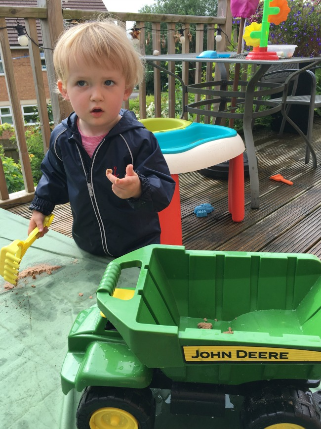 Trains-romans-and-bikes-toddler-in-puddle-suit-in-garden