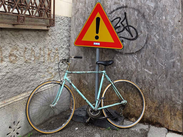 Bicycle locked to a temporary general warning sign, via Roma