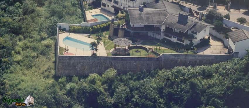 Construção da residência com construção da piscina com esse muro de arrimo com pedras com até 7 m de altura pois o proprietário queria que a construção da piscina ficasse no mesmo nível do piso da residência. Executamos o quiosque com telhas com a execução do paisagismo.