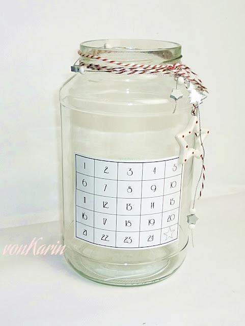 Gurkenglas mit Kalendarium und Kerze als Adventskalender