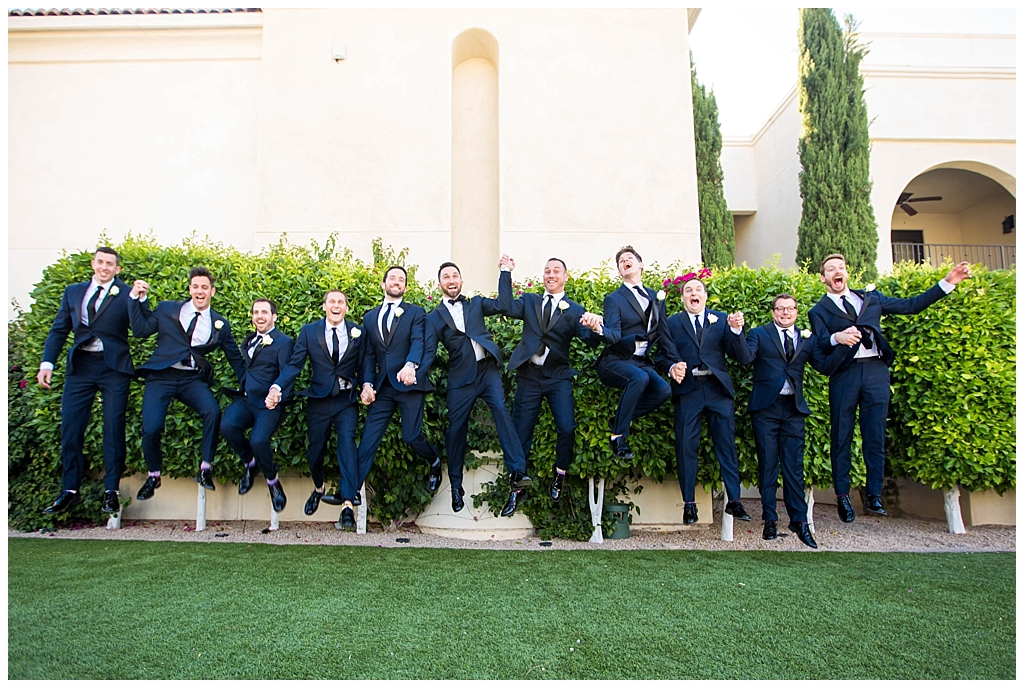 Groom and groomsmen jumping in navy blue suits at Omni Montelucia