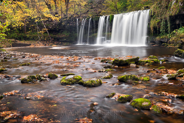 Autumn leaves lie on the Nedd Fechan below Upper Gushing Falls by Martyn Ferry Photography