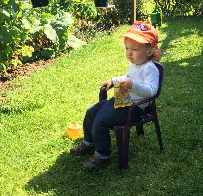 toddler-sat-on-chair-in-garden