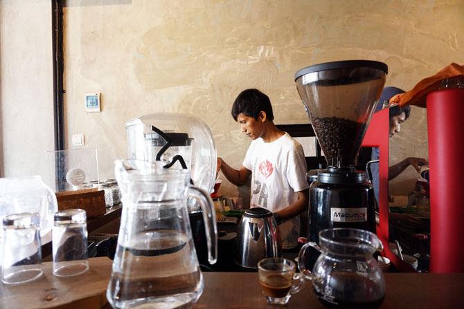 Menuangkan biji kopi ke grinder atau alat penggiling biji kopi