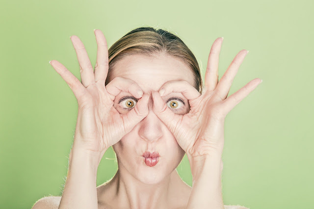 Funny woman using hands as mask, eyes