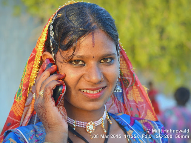 Gypsy woman; young woman; Matt Hahnewald Photography; Facing the World; photography; photo; image; outstanding; fantastic; favourite; superior; excellent; vibrant; Nikon D3100; Nikkor AF-S 50mm f/1.8G; prime lens; 50mm; 4 : 3 aspect ratio; horizontal format; closeup; portrait; street portrait; headshot; outdoor; colourful; world cultures; character; personality; real people; human head; human face; human eyes; facial expression; eye contact; headscarf; consent; rapport; respect; encounter; ethnic portrait; travel; ethnic; tribal portrait; tradition; India; one person; female; authentic; fascinating; emotion; adorable; right hand; henna hands; henna tattoo; cell phone; sunset; warm light; Jaisalmer; Rajasthan; lips; sensual; almond eyes; teeth; smiling; colourful veil; attractive; exotic; charming; incredible; colourful headscarf; posing; fabulous; beautiful; gorgeous; breathtaking
