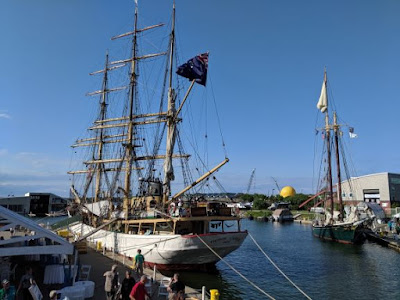 Sailing ship with 3 masts sits at dock with a 2-masted ship to its right