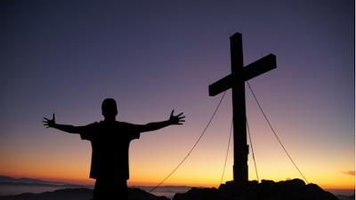 homen enfrente de uma cruz
