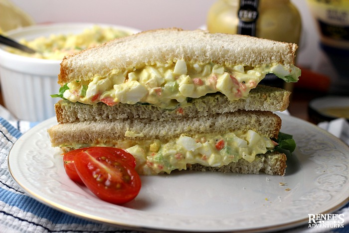 Cut and stacked egg salad sandwich on a white plate