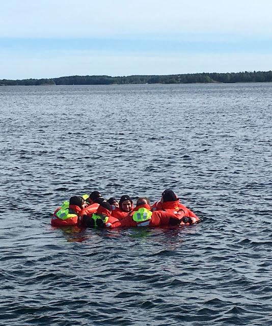 9 kartoittajaa pelastautumispuvuissa yhdessä läjässä kellumassa.