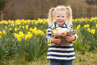 Photo of a Smiling Little Girl Holding a Basket of Easter Eggs Outside