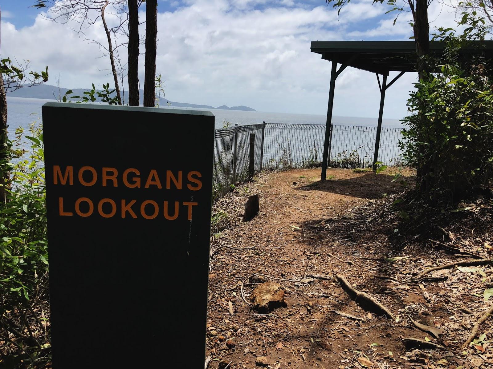 Zdjęcie drewnianego znaku w australijskim miasteczku Mission Beach informującego o tym, że znajdujemy się na puncie widokowym Morgana. W oddali widać sam punkt, a z niego Morze Koralowe.