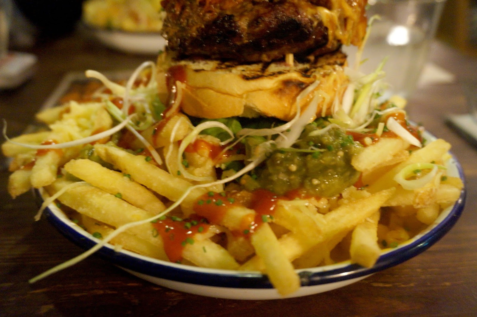 Close up of burger with bacon, fries and mac and cheese