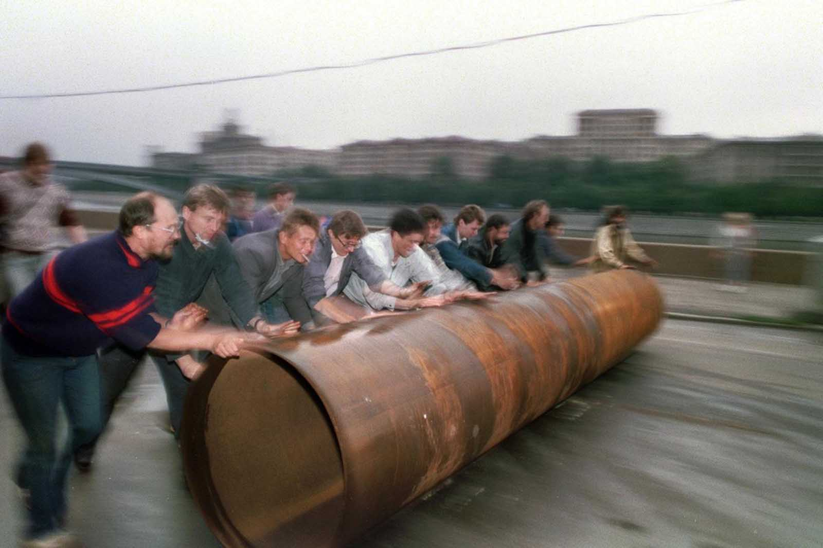 Supporters of Russian president Yeltsin roll a large metal pipe to use as a barricade near the Russian federation building in Moscow, on August 19, 1991, following a military coup attempt by Soviet hardliners.
