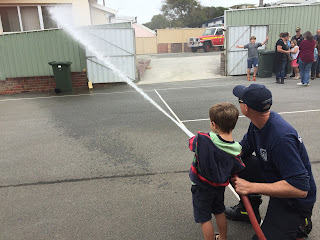 child with hose on home ed trip to Albany Fire station