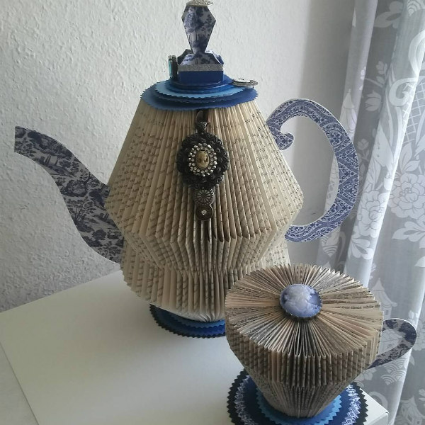 Folded book teacup and teapot with decorative elements and patterned paper handles, spout and base