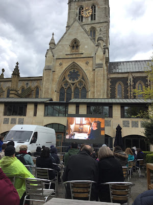 Pic of seated audience in front of All's Well That Ends Well screening with Southwark Cathedral in background