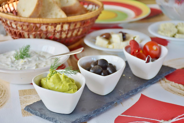 guacomole tomotoes olives in dishes