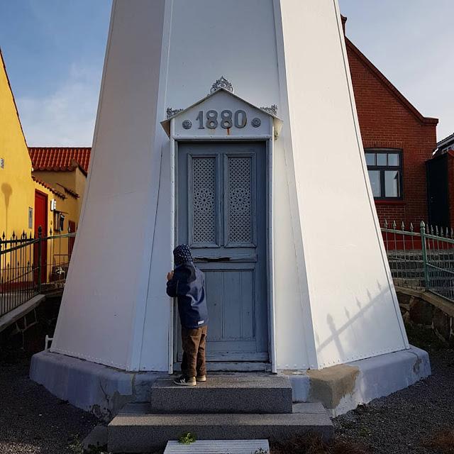 Bornholm mit Kindern im Herbst. Teil 3: 10 tolle Ausflugsziele für Familien auf Dänemarks Sonneninsel. Der weiße Leuchtturm von Rönne leuchtet im Herbst in der Sonne.