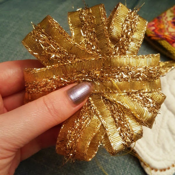 hand holding gold ribbon rosette with needle and thread stitching it together