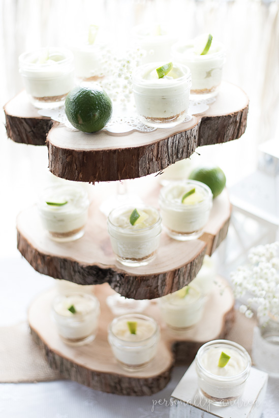 Rustic and romantic spring bridal shower | Three tiered wood slice serving piece with mini individual lime cheesecakes in mason jars | personallyandrea.com