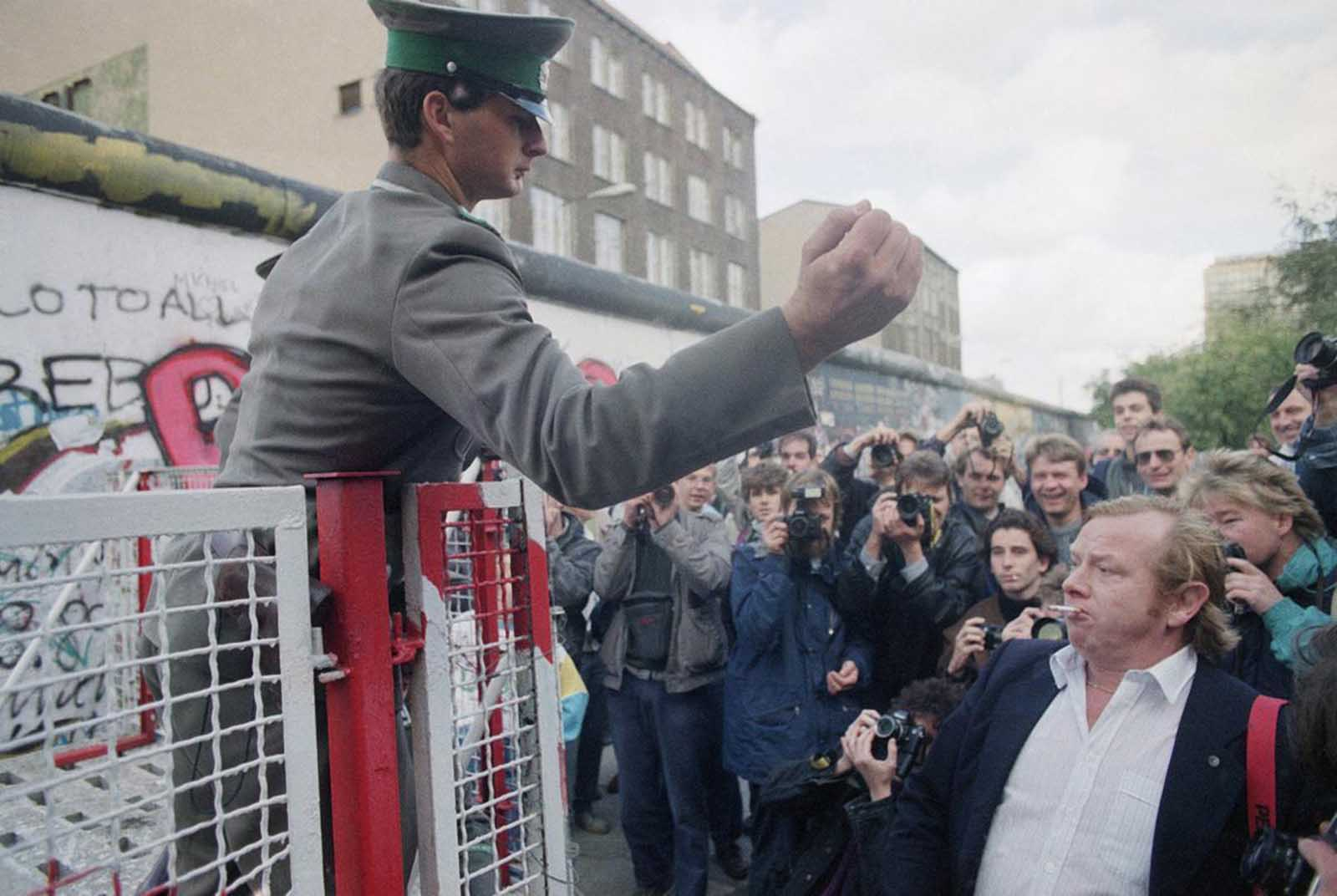 An unidentified East German border guard gestures toward some demonstrators, who who threw bottles on the eastern side of newly-erected barriers at the Checkpoint Charlie crossing point on October 7, 1989.