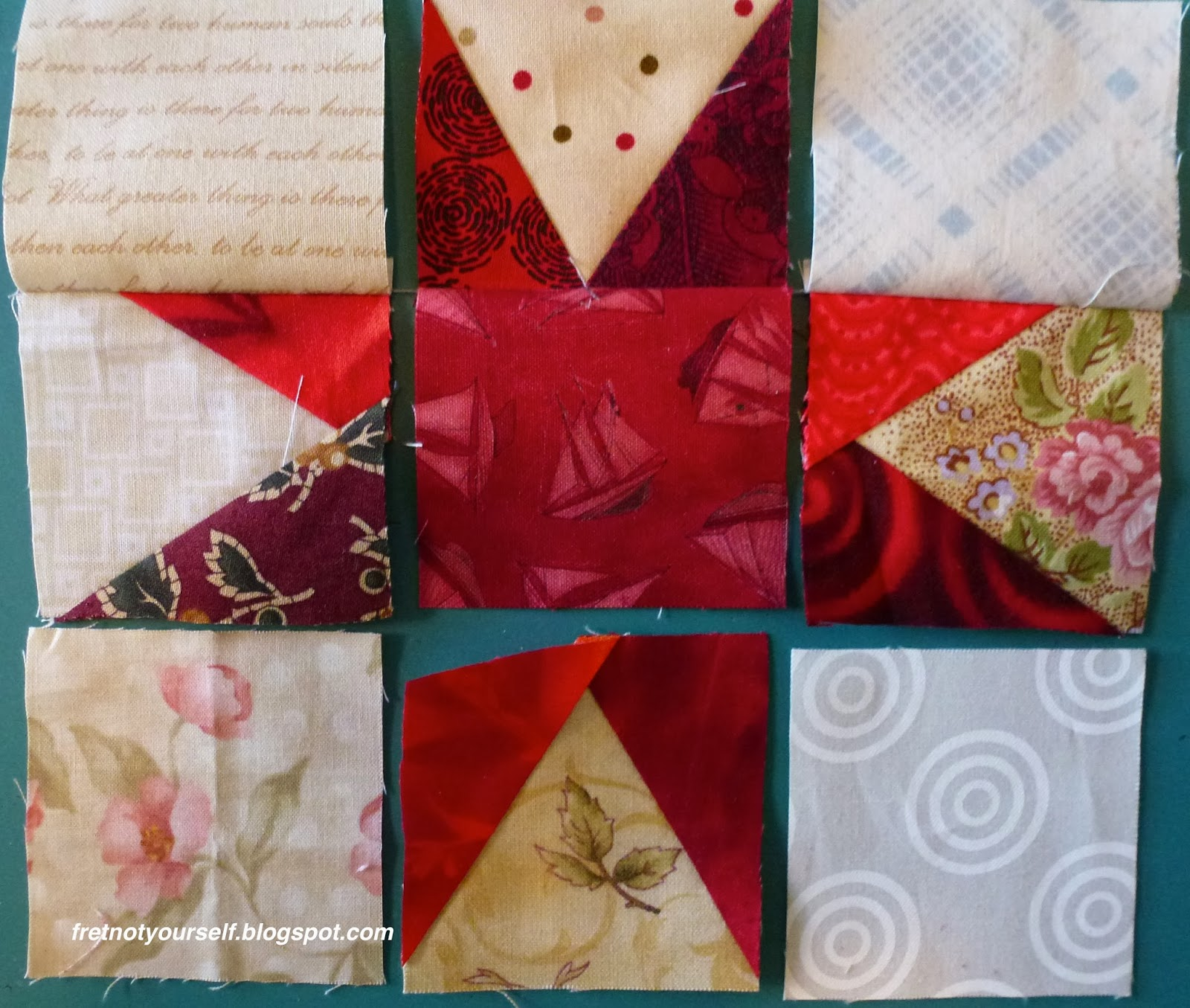 Layout of red and cream nine-patch block showing three pairs of squares sewn with chain piecing intact between them.
