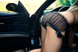 model escort in black lace and chiffon panties leaning into car