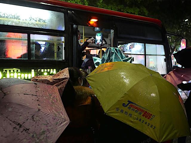 Person boarding a bus with a yellow Jumbo Wuzhou Bus umbrella.
