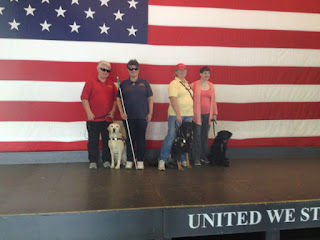 Dixie Landers in front of large flag on Yorktown Hangar Deck