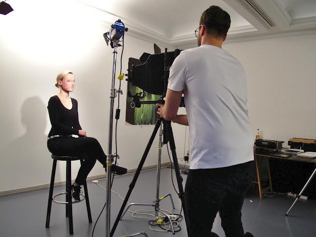 Fotograf fotografiert Frau auf Stuhl mit Großbildkamera