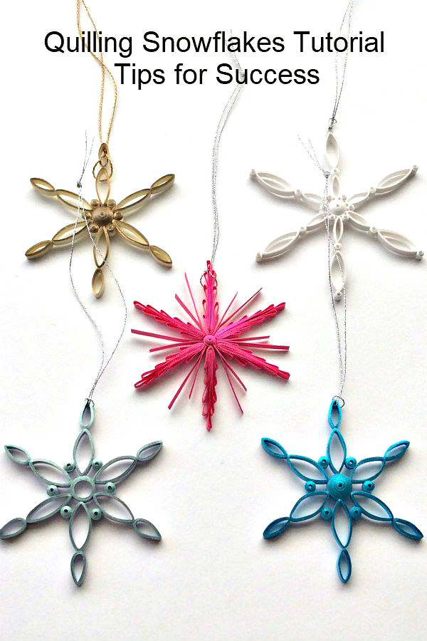 five quilled snowflake ornaments made with brightly colored metallic edge quilling strips