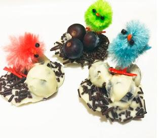 pequeños nidos con fideos de chocolate, y bolas de chocolate blanco rellenas de arandanos, con unos pollitos para decorar de juguete
