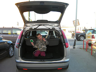 boy in boot of car