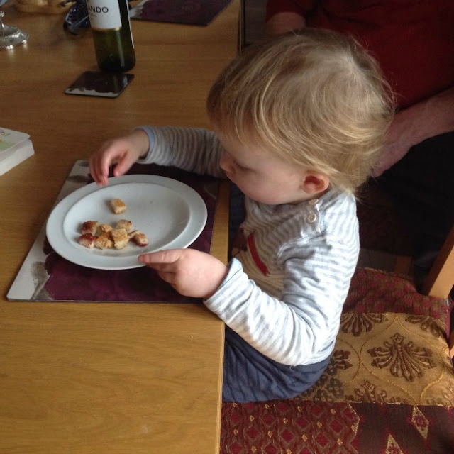 toddler sat on chair at table eating toast
