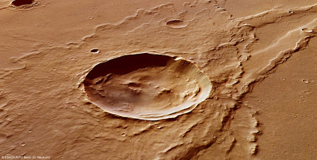An impact crater on Mars, named Melas Dorsa, and its surroundings show a rich geologic history. The image was created by the European Space Agency's Mars Express. Studies of the transformation of a synthetic version of a mineral known as whitlockite suggest that Mars had a more water-rich past than previously thought. (Credit: G. Neukum/ESA,DLR, FU Berlin)