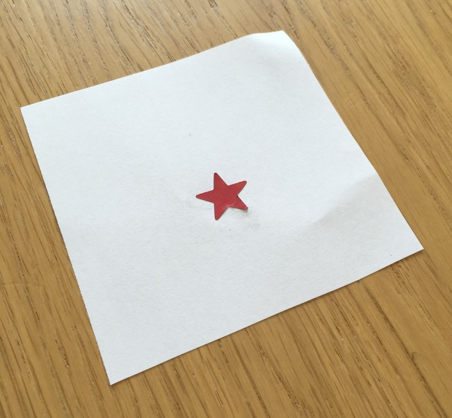 one red star on a square of white paper