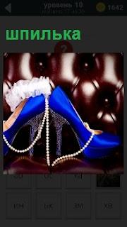 Женские туфли на высокой шпильке, на которые наброшены красивые бусы на фоне кожаного кресла