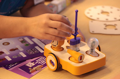 A student hand is reaching to work on a Kibo robot.