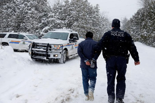 FILE PHOTO: A man who told police that he was from Sudan is taken into custody by a Royal Canadian Mounted Police (RCMP) officer after arriving by taxi and walking across the U.S.-Canada border into Hemmingford, Quebec, Canada on February 13, 2017. REUTERS/Christinne Muschi/File Photo