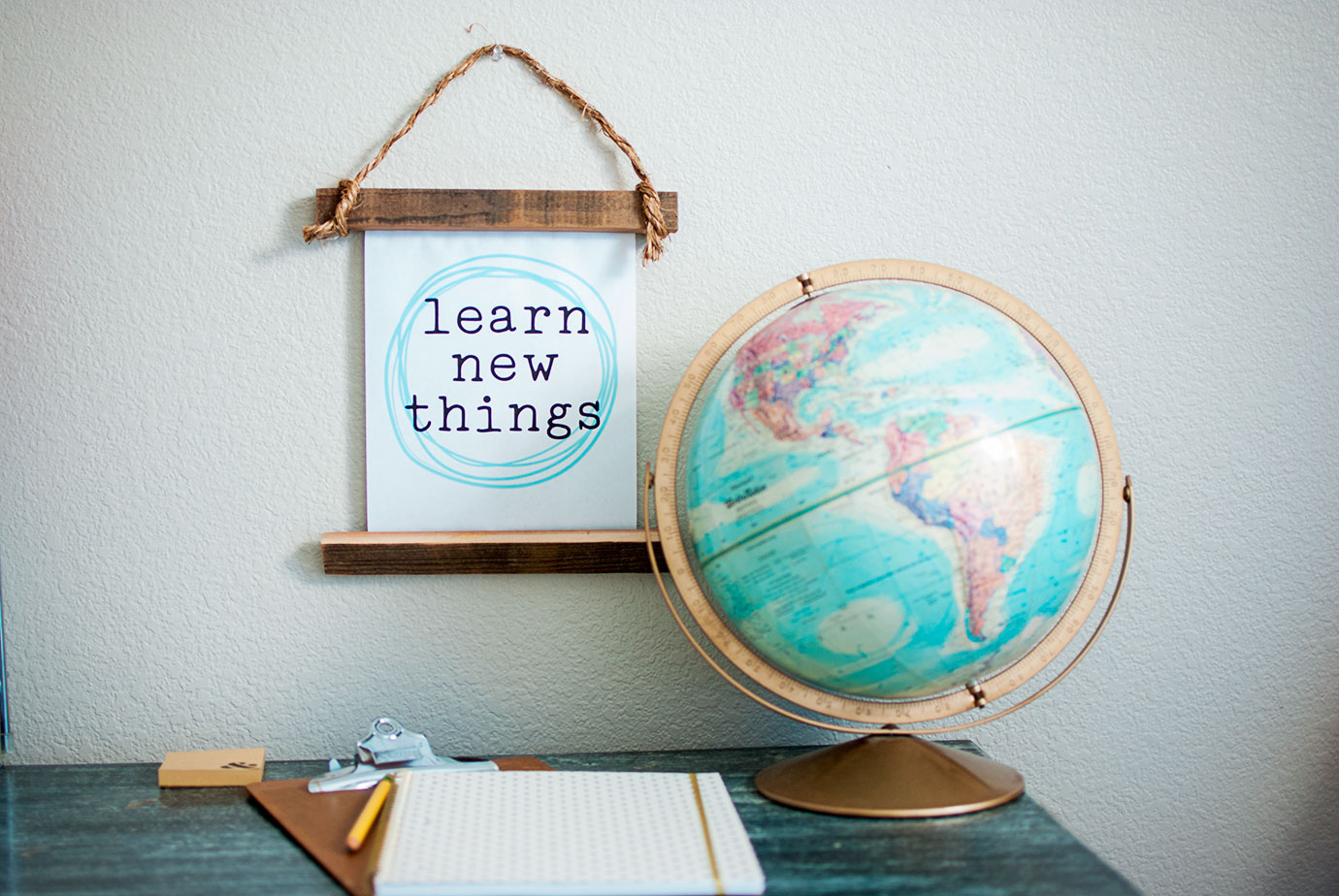 Learn New Things Printable and DIY Project on a desk with a globe and notebook