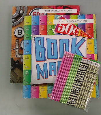Two colorfully-decorated portfolios, one on top of the other and each printed with the words, 'Book Marks.' Strips of label-maker tape have been put across the top of each one, reading, 'COST: ONE ROCK-STAR EACH.' Sitting on top of the two portfolios are several novelty-printed pencils, held together in clear-plastic packaging. From left to right, the pencils are pink-patterned, light green-patterned, black-against-pale-green zebra-patterned, and money-patterned, with about four of each variety visible.