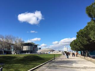 Parque das Nações área livre com o oceanário do lado direito, pessoas caminhando