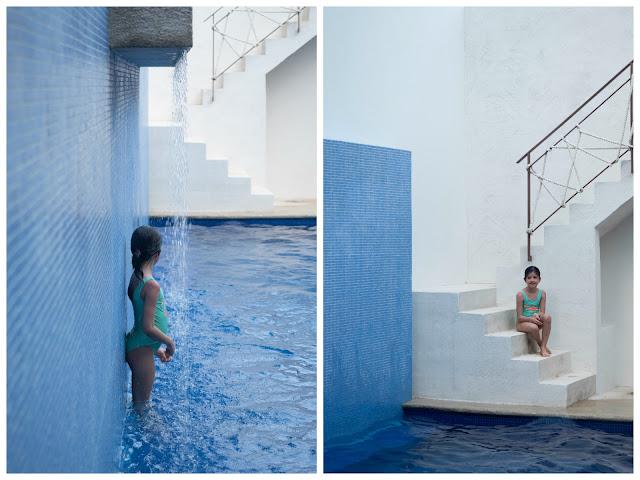 Niña bajo una cascada en una piscina azul y sentada en las escaleras de la piscina