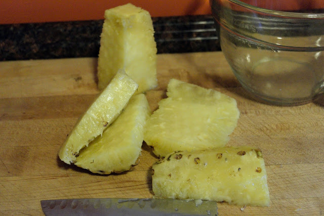 A pineapple, on a cutting board, with the cheeks cut off.