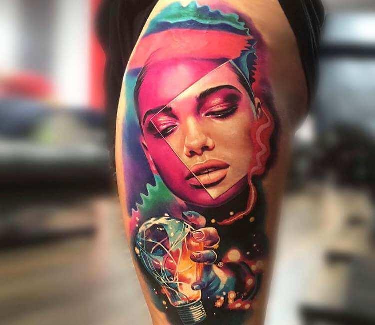 Tatuaje de un rostro cósmico agarrando una bola de cristal